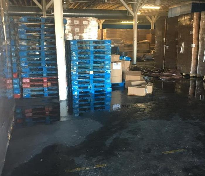 Garage with blue pallets sitting in water.