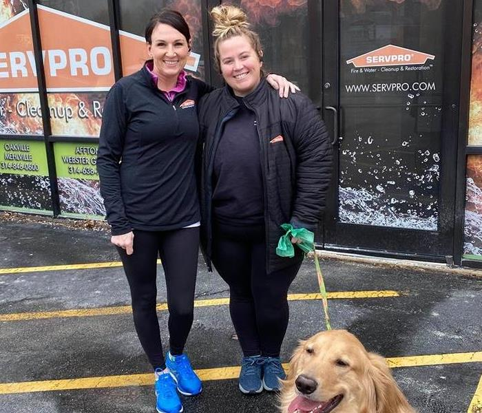 Two people outside of a SERVPRO with a golden retriever.