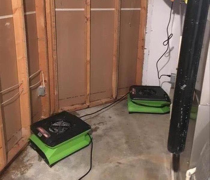 Green air movers on a concrete floor.