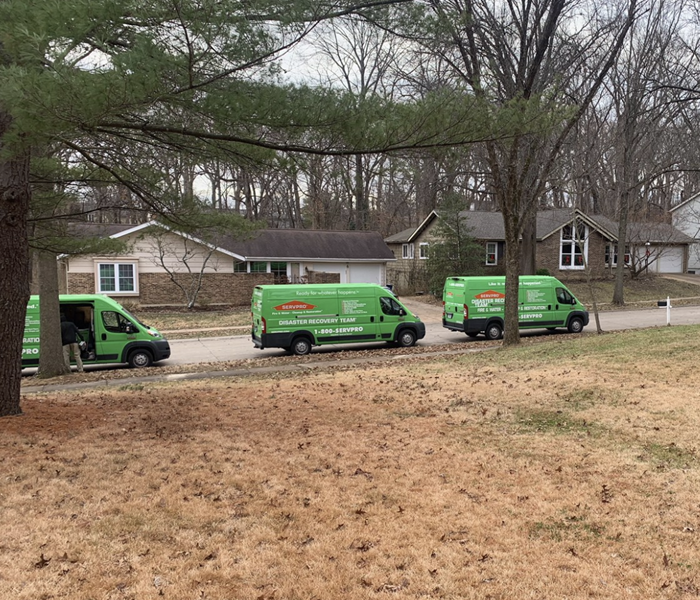 Three green trucks park on the side of a street.