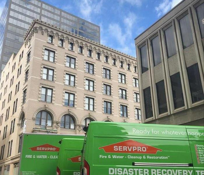 SERVPRO van parked in front of a tall grey building.