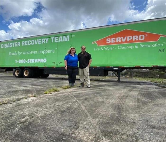 Two people in front of a green SERVPRO trailer.