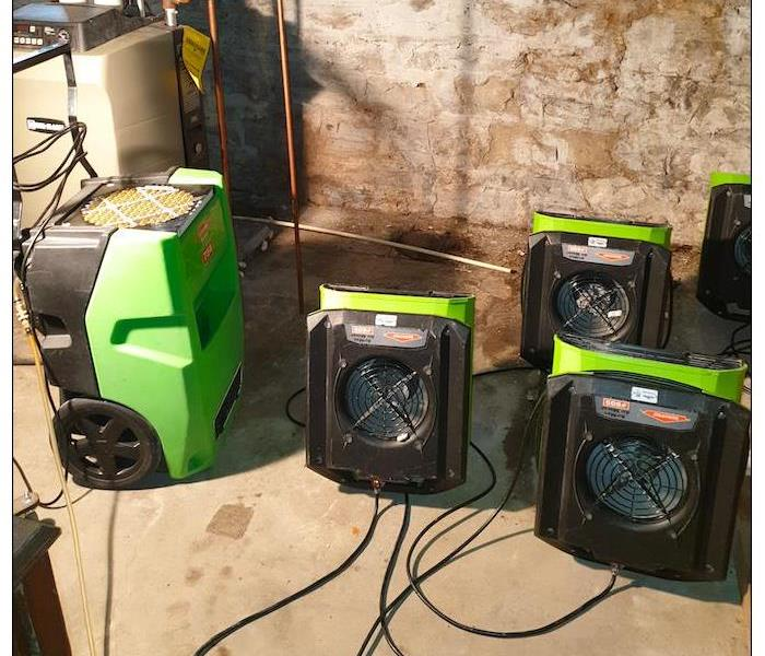 Green air movers and scrubbers in a dirty room.