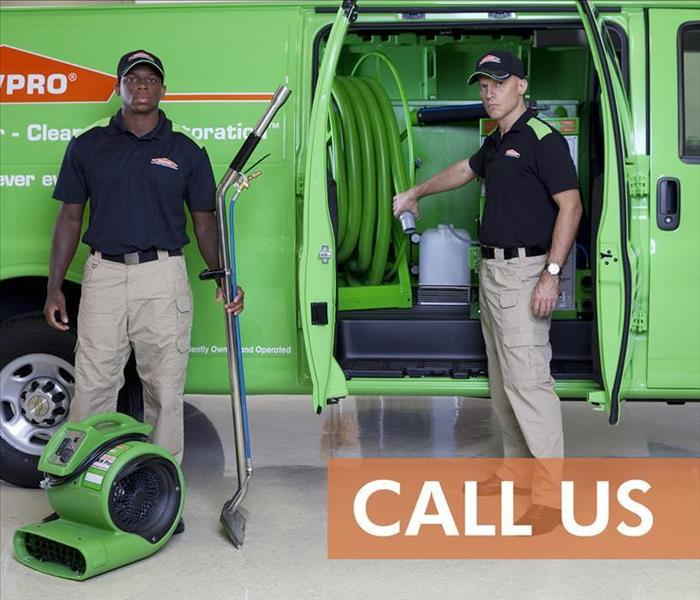 Two SERVPRO technicians with drying equipment and a SERVPRO van behind them
